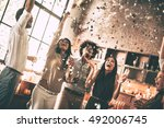 Moments of happiness. Cheerful young people throwing confetti and smiling while enjoying home party on the kitchen  - stock photo