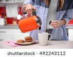 Woman Making Tea In Kitchen
