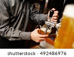 barman pours beer into a glass... | Shutterstock . vector #492486976