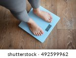 Stock photo female bare feet standing on a scales 492599962