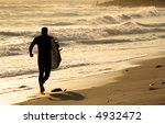 Surfer running on the beach at sunset - stock photo