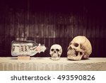 Small photo of Human Skull with Ship in a Bottle with black background / Still life style