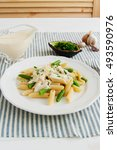 Small photo of Penne and french bean with alfredo sauce on a striped tablecloth.
