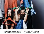 Small photo of Fashion couple denuded tired of brunette girl with red hangers and bearded man with green high heels shoes among clothes to wear near rack in closet