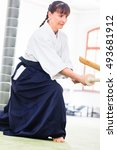 Small photo of Woman fighting with wooden swords at Aikido training in martial arts school