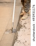 Small photo of A concrete finisher using a walking edger tool on wet concrete.