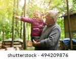 Stock photo granddaughter pointing with finger her grandfather something in forest 494209876