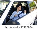 car safety: female driver fastening seat belt - stock photo
