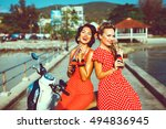 Beautiful young girls in style pin-up blonde and brunette drink Cola in bottles, posing on the pier next to the scooter, fun, smile, beautiful makeup