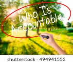Small photo of Woman Hand Writing Who Is Accountable? on blank transparent board with a marker isolated over green field background. Business concept. Stock Photo