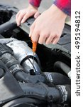 Small photo of Checking Car Engine Oil Level Under Hood With Dipstick