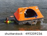 Small photo of URK, THE NETHERLANDS - SEP 24: Rescue worker showing how to use a life raft on September 24, 2016 in the harbor of Urk, the Netherlands