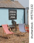 Small photo of Stripey Deck Chairs on beach near fish shop