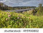 Steel bridge overpass on concrete piers, a highway crosses the Russian forest, sunny summer day. - stock photo