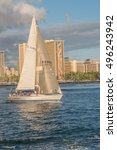 Small photo of Honolulu, Hawaii, USA, Oct. 10, 2016: Sleek silver sailboat departing the Ala Moana Channel with Waikiki hotels in the background.