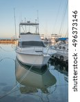 Small photo of Honolulu, Hawaii, USA, Oct. 10, 2016: Profile view of a modern white and black sport fishing boat with a background of the Ala Wai Harbor.
