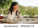 happy young woman sitting at... | Shutterstock . vector #496446772