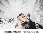 Happy newlyweds under the bridal veil