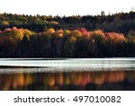 Small photo of Autumn Sunset on Pickett Lake (New Brunswick Canada) - sun has almost gone down and is just touching the tops of the trees