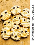 Small photo of Scared little mummified monster cookies piled on old rustic kitchen bench. Halloween baking treats