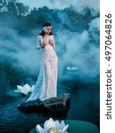 Small photo of Beautiful fairy in a beautiful white garment, sits on a rock in water.A wreath made of shells, handmade.Among picturesque forests, mysterious,alluring lakes.Mystical photo shoot.Fashionable toning.