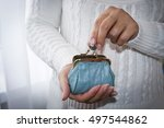 Young Woman Putting Coin In...