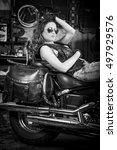 Small photo of Beautiful girl sits on an abrupt black motorbike, stylish girl with wavy hair and sunglasses on bike in the garage