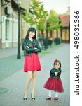 Small photo of Beautiful young mother and daughter dressed alike(5)