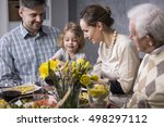 Small photo of Smiling young marriage with a little child sitting at a table during an elegant family meeting