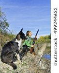 Small photo of The girl-hunter with a dog in an ambush,Siberia