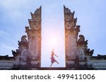 Stock photo woman traveler jumping with energy and vitality in the gate of a temple bali indonesia 499411006