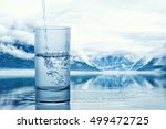 Pouring water into a glass against the nature landscape - stock photo