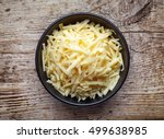 Bowl Of Grated Cheese On Woode...