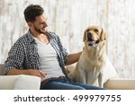Stock photo young bearded guy stroking his dog indoors 499979755