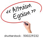 Small photo of Women Hand writing Altruism - Egoism with black marker on visual screen. Isolated on white. Business, technology, internet concept. Stock Photo