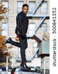 Small photo of Young afro american man jumping in the street, with a classic style