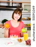 Young happy woman with apple and orange - stock photo
