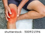 Small photo of Older man puts both hands on an aching knee.