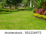 Backyard, landscape design With multicolored shrubs intersecting with flower bright green lawns Behind the house is a modern, garden care service, green grass with a beautiful yard for the background. - stock photo