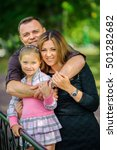 Small photo of the girl with mother and the father walks in the park, all together hold hands and smile