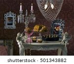 Small photo of Vintage table of cakes, muffins and biscuits. Dessert. A lot of decorations. Wallpaper and paintings in the background. Crystal candle holder and a chandelier. Absurd food image. Picturesque lighting.