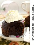 Small photo of Chocolate fondant, souffle cake with whipped cream on decorative plate