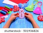 child holds a felt snowman...