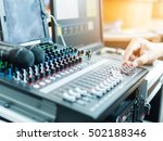 Small photo of Hand of Technician using Sound system mixing audio equipment board on stage with soft light,selective focus