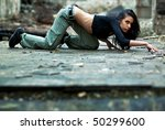 Young woman in a ruined building. Secretly crawling on a floor. - stock photo