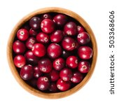 Small photo of Fresh cranberries in a wooden bowl on white background. Ripe berries of Vaccinium macrocarpon, also large cranberry, American cranberry or bearberry. Isolated macro food photo close up from above.