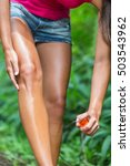 Small photo of Woman spraying mosquito repellent on leg skin. Woman using Insect repellent bug spray bottle on legs, body and clothing outdoor in nature forest. Prevention for zika virus affecting tropical areas.