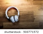 Small photo of Blue headphones on wooden background with soft light vintage style easy listening concept.