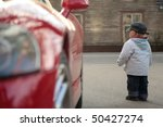 Small photo of small boy near red sport machine, back