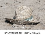 An Old Straw Hat On The Sand